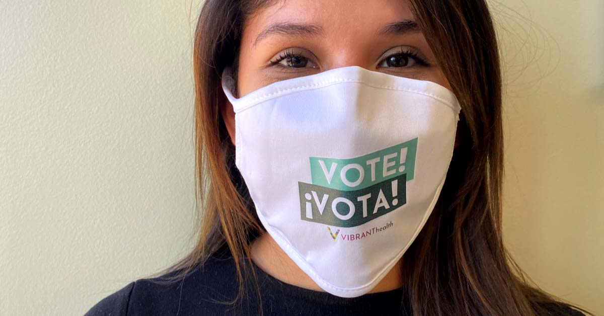 """Woman wearing mask with """"Vote!"""" printed across the front."""